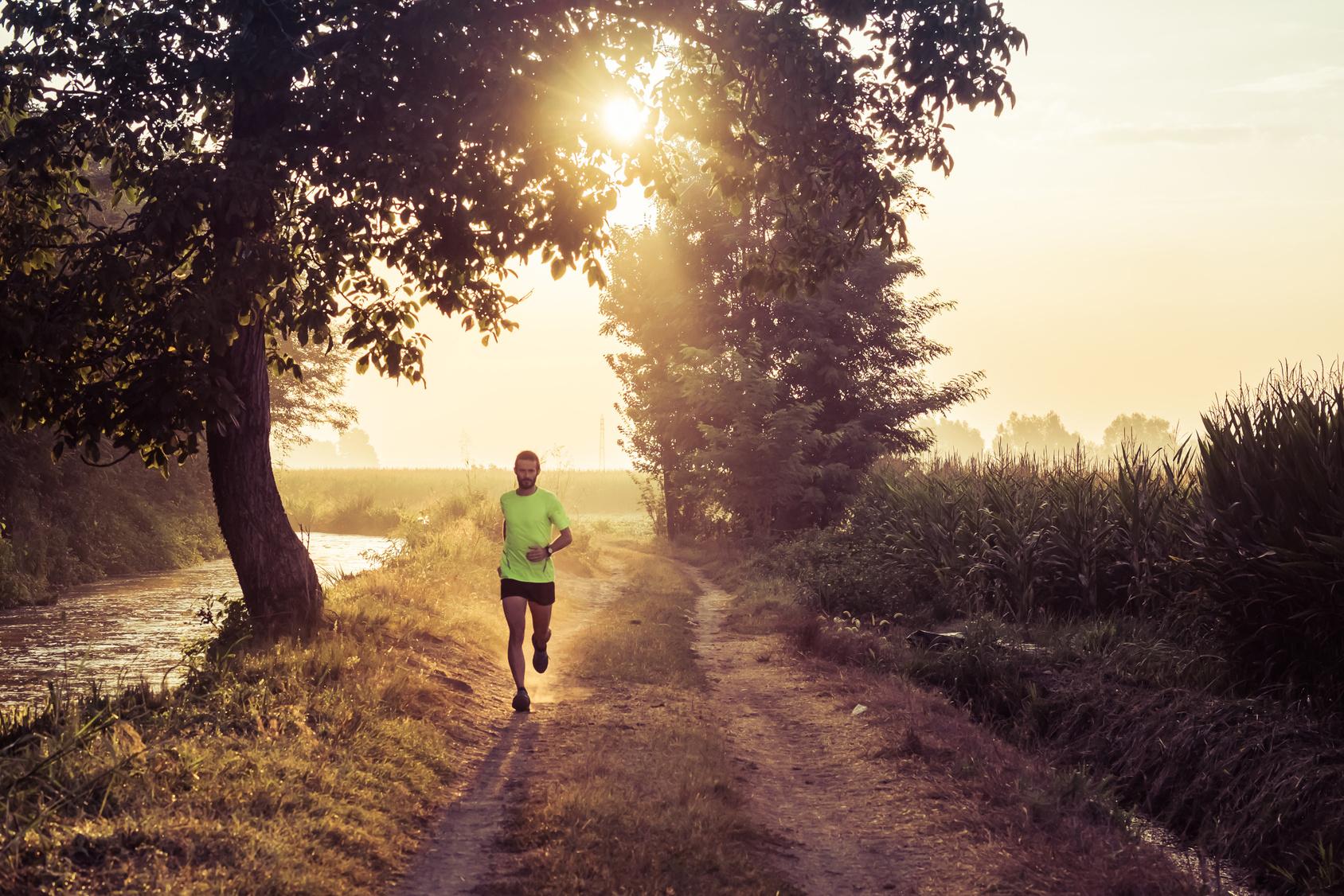 Ragazzo che corre all'alba su strada di campagna in estate