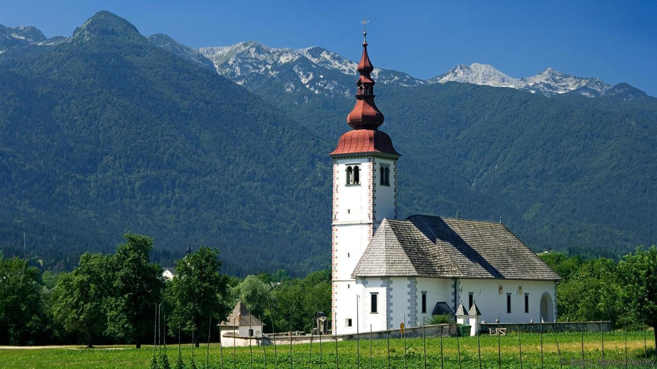 AJ3XN4 The church at Bitjne near lake Bohinj stands out in stark beauty against the surrounding mountains. Image shot 2006. Exact date unknown.